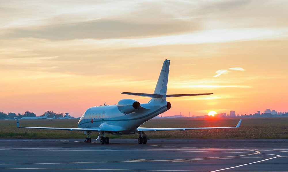 a charter jet taxiing on runway at sunset